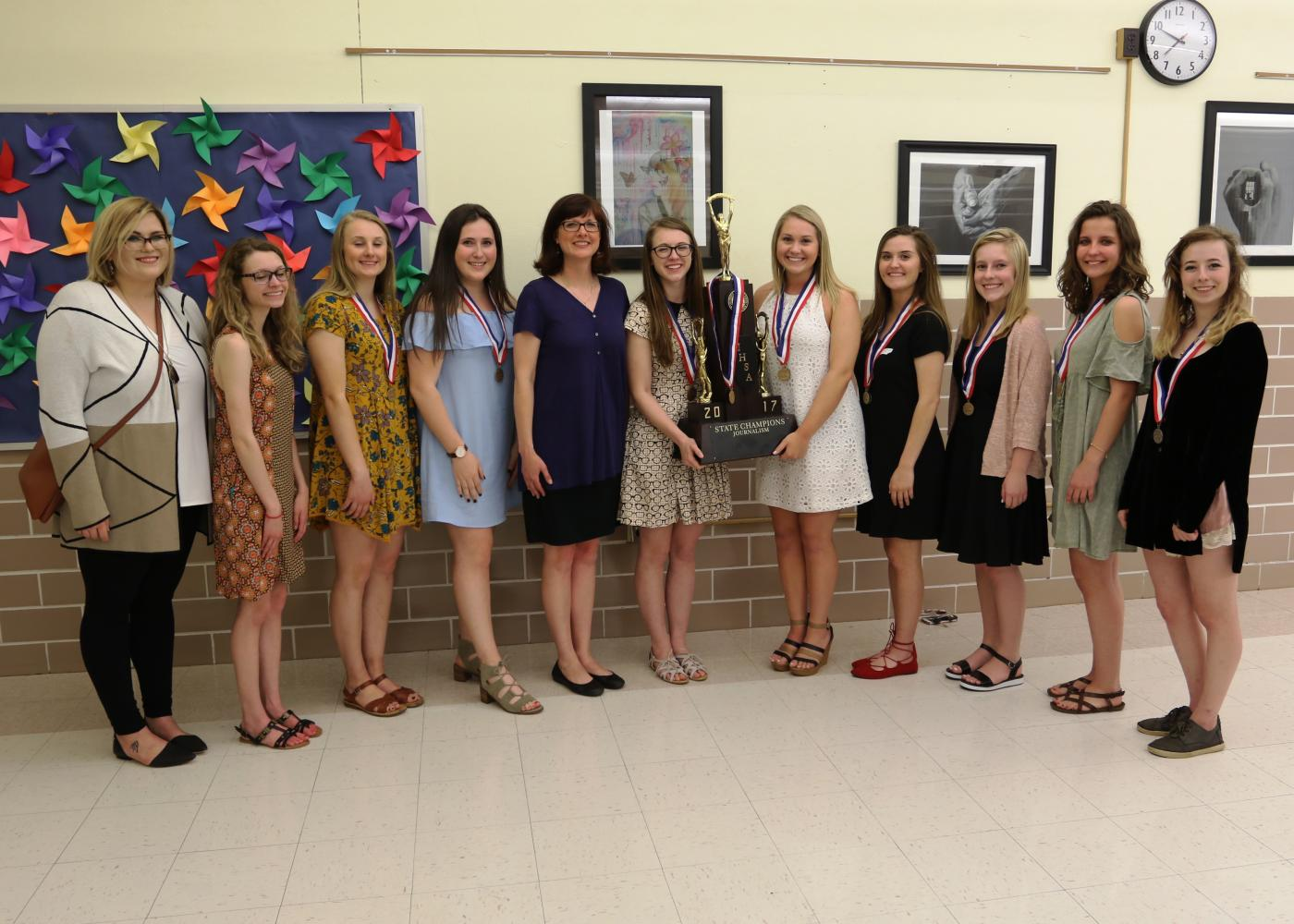 Nine members and the two advisers of the EHS journalism team stand next to the championship trophy at the District 7 School Board Meeting on May 8. From left: Ms. Mudge, Maddi Lammert, Jane Thompson, Jamie Skigen, Mrs. Thrun, Erin Morrisey, Morgan Goebel, Emma Lipe, Sophie Kraus, Jade Weber and Nara Markowitz.