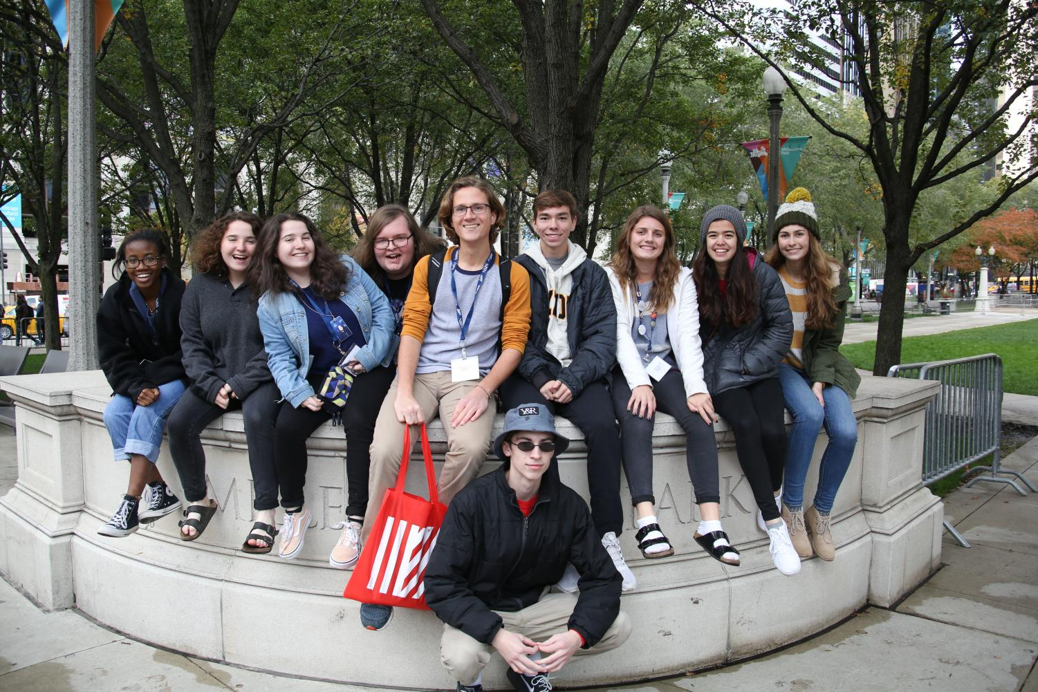 Journalism students pose on the sign in front of Millennium Park