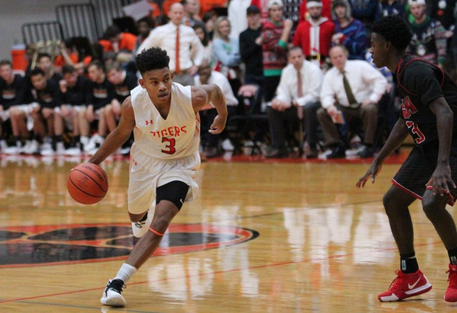 Senior+Malik+Robinson+dribbles+the+ball+down+the+court+in+a+home+game+on+Dec.+14.