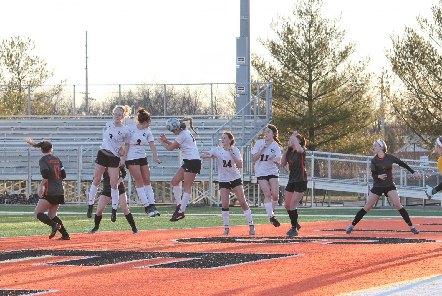 Three varsity girls soccer players jump to head the ball off of a corner kick on March 16.