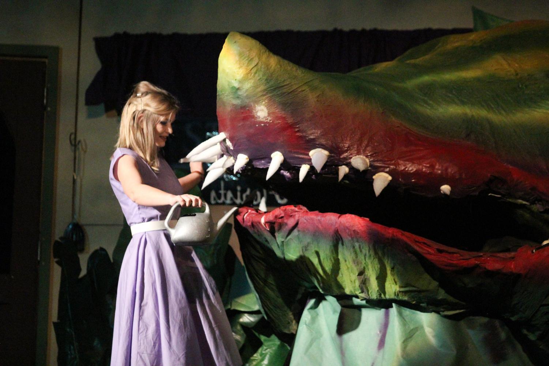 Audrey (senior Riley Stroehmer) feeds Audrey 2, a carnivorous plant.
