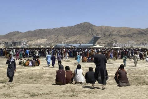 Families wait outside the perimeter of the airport in Kabul on Aug. 16.