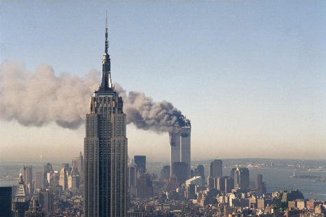 In this Sept. 11, 2001,  photo, the twin towers of the World Trade Center burn behind the Empire State Building in New York City.