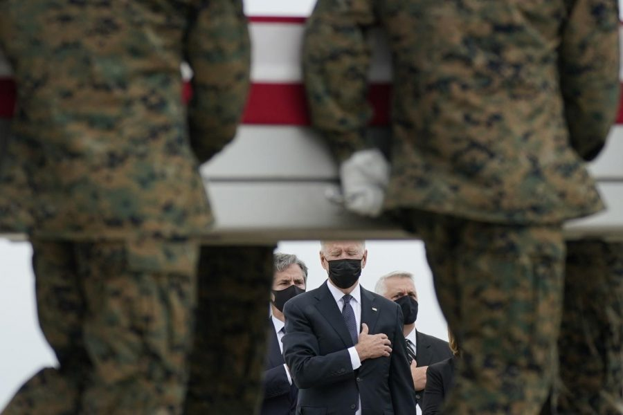 President Joe Biden watches as the remains of the 13 service members killed during the Kabul airport attack are carried off the transport at Dover Air Force Base.