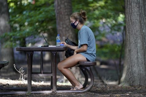 A student works outside of Ehrighaus dormitory at the University of North Carolina in Chapel Hill, Tuesday, Aug. 18, 2020.