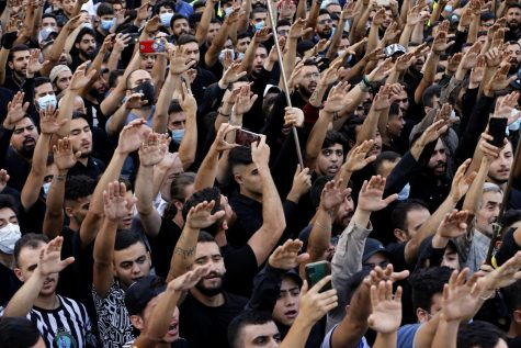 Large groups of Lebanese mourners raised their hands at the funeral of three Hezbollah supporters killed Thursday.
